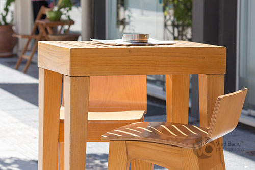 wooden coffee table with astray and stool on a terrace in a sunny day